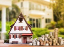 toy house next to stacks of coins, why you need high-value home insurance
