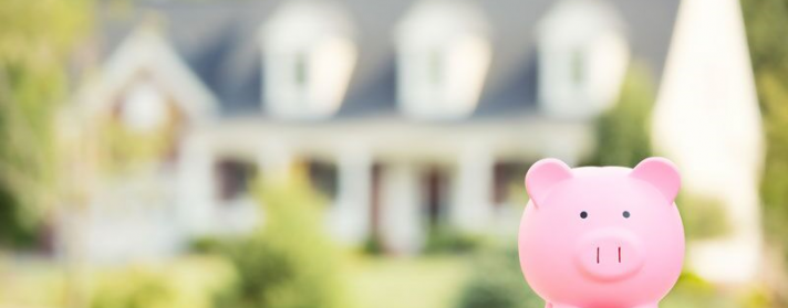 piggy bank in front of home, save on your first home policy